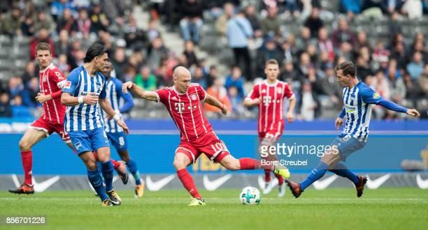 Arjen Robben of FC Bayern Muenchen is challenged by Vladimir Darida of Hertha BSC and Karim Rekik of Hertha BSC during the Bundesliga match between...