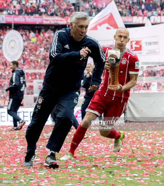 Arjen Robben of FC Bayern Muenchen tries to shower his head coach Carlo Ancelotti with beer in celebration of the 67th German Championship title...