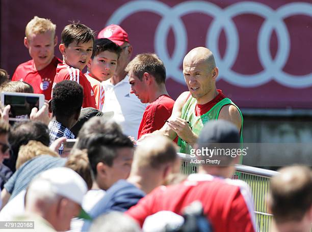 Arjen Robben of FC Bayern signs autographs during training at the FC Bayern Muenchen training grounds on July 1 2015 in Munich Germany