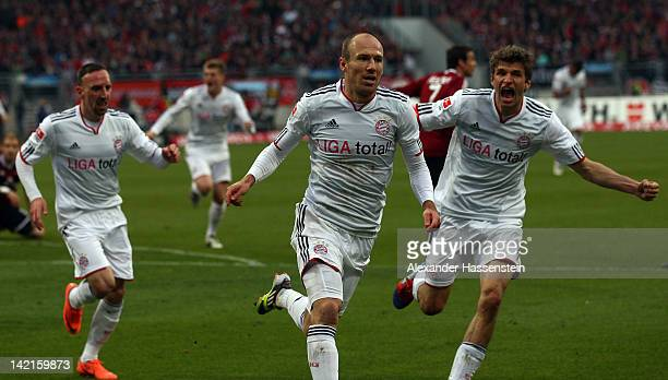 Arjen Robben of Muenchen celebrates scoring the first goal with his team mate Thomas Mueller and Franck Ribery during the Bundesliga match between...