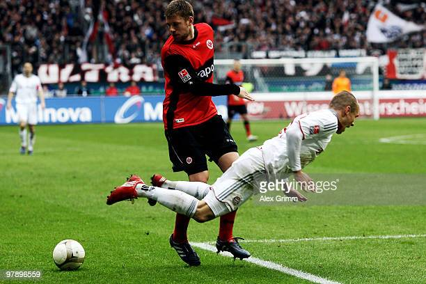 Arjen Robben of Muenchen is challenged by Marco Russ of Frankfurt during the Bundesliga match between Eintracht Frankfurt and Bayern Muenchen at the...