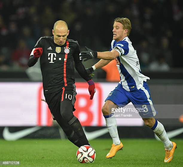 Arjen Robben of Muenchen is challenged by Per Ciljan Skelbred of Berlin during the Bundesliga match between Hertha BSC and FC Bayern Muenchen at...
