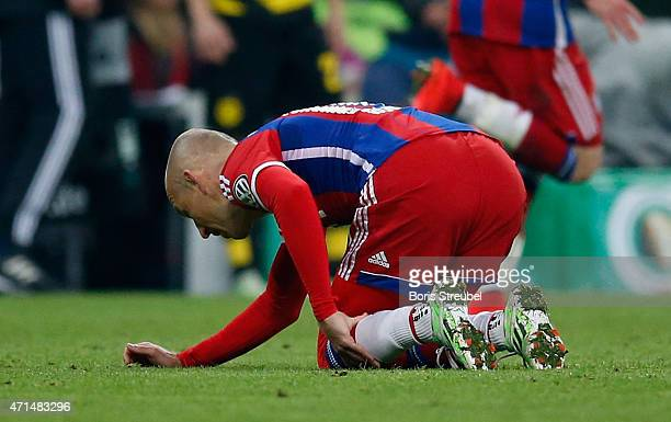 Arjen Robben of Muenchen knees off the pitch after receiving an injury during the DFB Cup semi final match between FC Bayern Muenchen and Borussia...
