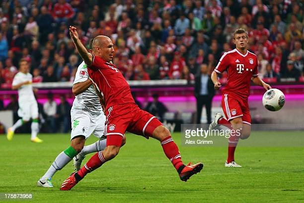 Arjen Robben of Muenchen scores his team's first goal against Alvaro Dominguez of Moenchengladbach during the Bundesliga match between Bayern...