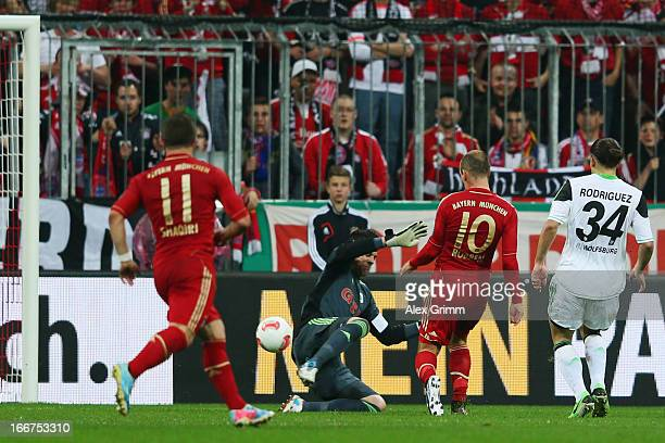 Arjen Robben of Muenchen scores his team's second goal against goalkeeper Diego Benaglio and Ricardo Rodriguez of Wolfsburg during the DFB Cup Semi...