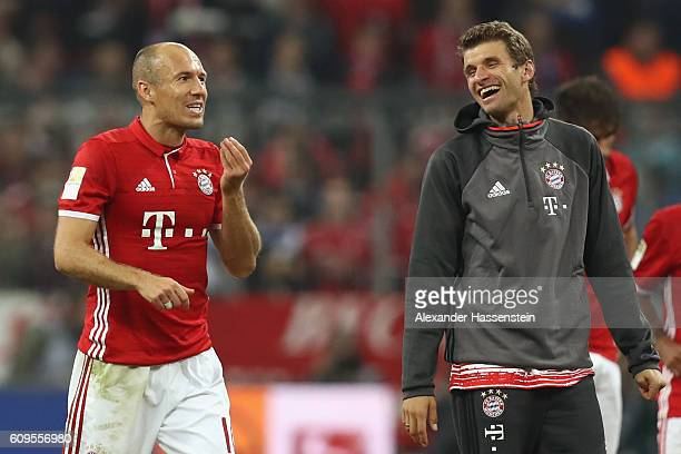 Arjen Robben of Muenchen smiles and celebrates victory with his team mate Thomas Mueller after winning the Bundesliga match between Bayern Muenchen...