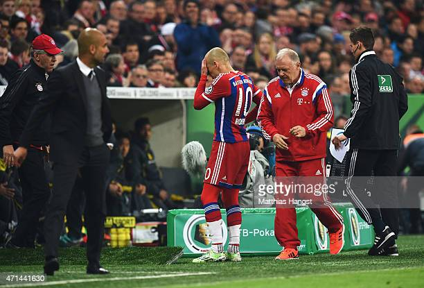 Arjen Robben of Muenchenwalks off the pitch injured as Josep Guardiola head coach of Muechen looks on during the DFB Cup semi final match between FC...