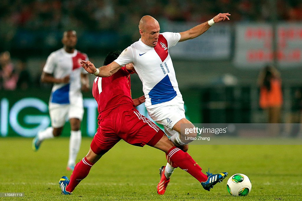 <a gi-track='captionPersonalityLinkClicked' href=/galleries/search?phrase=Arjen+Robben&family=editorial&specificpeople=194740 ng-click='$event.stopPropagation()'>Arjen Robben</a> (R) of Netherlands challenges <a gi-track='captionPersonalityLinkClicked' href=/galleries/search?phrase=Zhao+Xuri&family=editorial&specificpeople=596391 ng-click='$event.stopPropagation()'>Zhao Xuri</a> of China during their international friendly soccer match at Beijing Workers' Stadium on June 11, 2013 in Beijing, China.