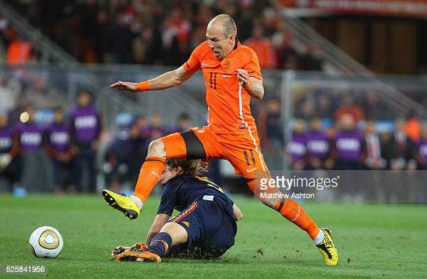 Arjen Robben of Netherlands jumps over Carles Puyol of Spain