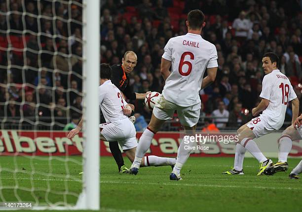 Arjen Robben of Netherlands scores his team's third goal past Leighton Baines Gary Cahill and Stewart Downing of England during the international...