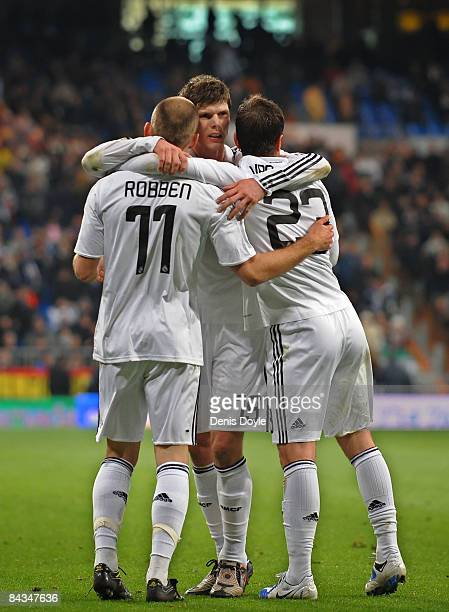 Arjen Robben of Real Madrid celebrates with Klaas Jan Huntelaar and Rafael Van Der Vaart after scoring Real's third goal against Osasuna during the...