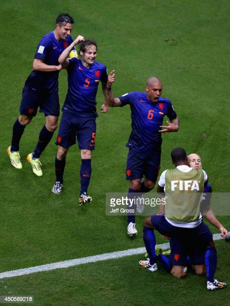Arjen Robben of the Netherlands celebrates his teams second goal with Robin van Persie Daley Blind and Nigel de Jong during the 2014 FIFA World Cup...