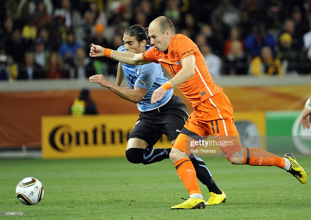 Arjen Robben of the Netherlands is challenged by Martin Caceres of Uruguay during the 2010 FIFA World Cup South Africa Semi Final match between...