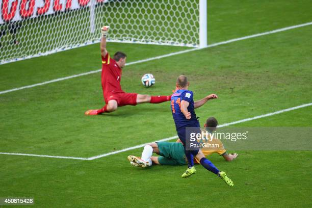 Arjen Robben of the Netherlands shoots and scores his team's first goal past goalkeeper Mathew Ryan of Australia during the 2014 FIFA World Cup...