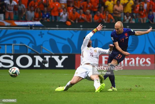 Arjen Robben of the Netherlands shoots and scores his team's second goal as Sergio Ramos of Spain defends in the second half during the 2014 FIFA...