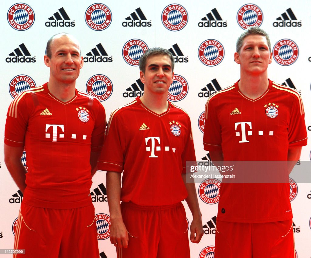 Arjen Robben (L) poses with his team mates Philipp Lahm (C) and Bastian Schweinsteiger in the new FC Bayern Muenchen home jersey for the season 2011/12 at Allianz Arena on April 19, 2011 in Munich, Germany.