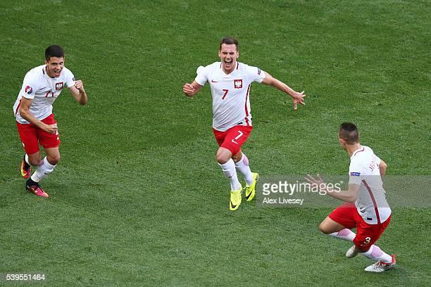 Arkadiusz Milik of Poland celebrates scoring his team's first goal with his team mates Artur Jedrzejczyk and Bartosz Kapustka during the UEFA EURO...