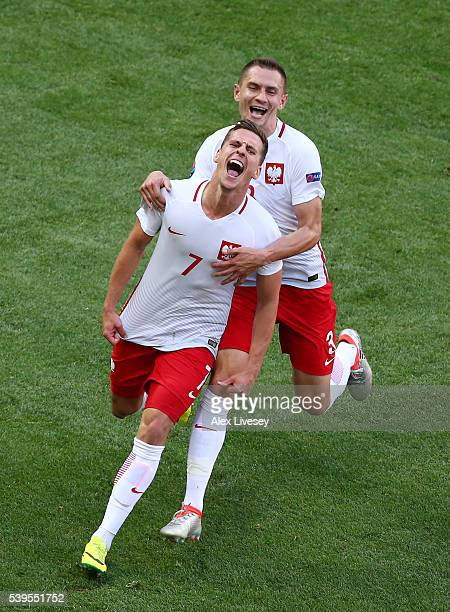 Arkadiusz Milik of Poland celebrates scoring his team's first goal with his team mate Artur Jedrzejczyk during the UEFA EURO 2016 Group C match...