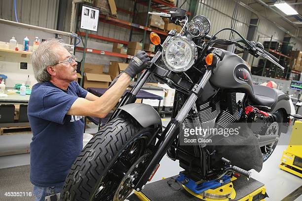 Arlan Reverts helps to put some finishing touches on a 2015 Victory Gunner motorcycle on the assembly line at the Polaris Industries factory on...