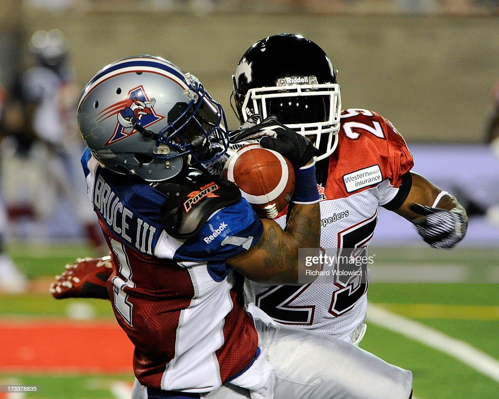 Arland Bruce #1 of the Montreal Alouettes catches the ball in front of Keon Raymond #25 of the Calgary Stampeders during the CFL game at Percival Molson Stadium on July 13, 2013 in Montreal, Quebec, Canada. The Stampeders defeated the Alouettes 22-14.