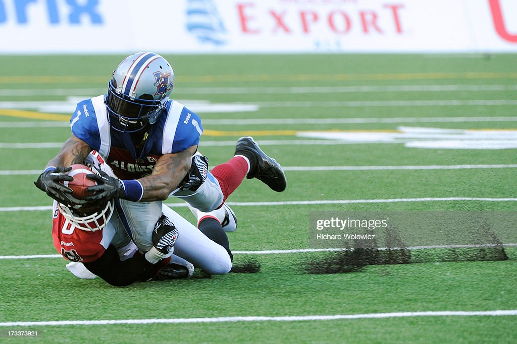 Arland Bruce #1 of the Montreal Alouettes dives with the ball after being tackled by Quincy Butler #0 of the Calgary Stampeders during the CFL game at Percival Molson Stadium on July 12, 2013 in Montreal, Quebec, Canada.