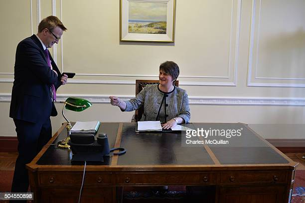 Arlene Foster asks to borrow a pen as she takes her seat in the First Ministers office after becoming the new First Minister on January 11 2016 in...