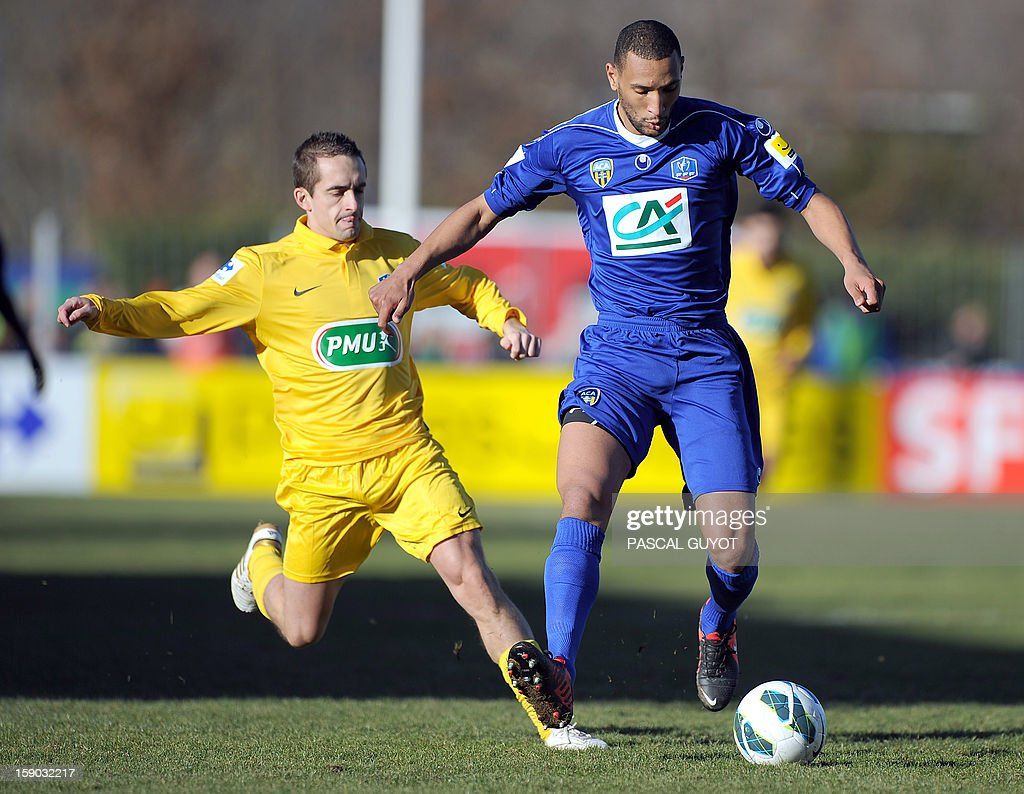Arles-Avignon's defender Yunis Abdelhamid (R) vies for the ball with Mende's forward Nicolas Brunel (L) during the French Cup football match between Mende and Arles-Avignon at the Jean Jacques Delmas stadium on January 6, 2013, in Mende.
