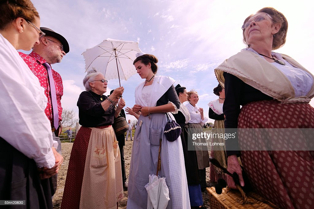 'Arlesiennes', so called traditional women, stand together while horsemen catch young bulls to brand them on May 26, 2016 in Saintes-Maries-de-la-Mer near Arles, France. The 'Guardians' celebrate the day in memory of the Marquis de Baroncelli and show tourist how they work. Marie Segretier (18) help them to wrangel the bulls and brand them. She is the only 'cow girl' in the area of Staintes-Maries-de-la-Mer (Camargue). She started with 5-6 years.