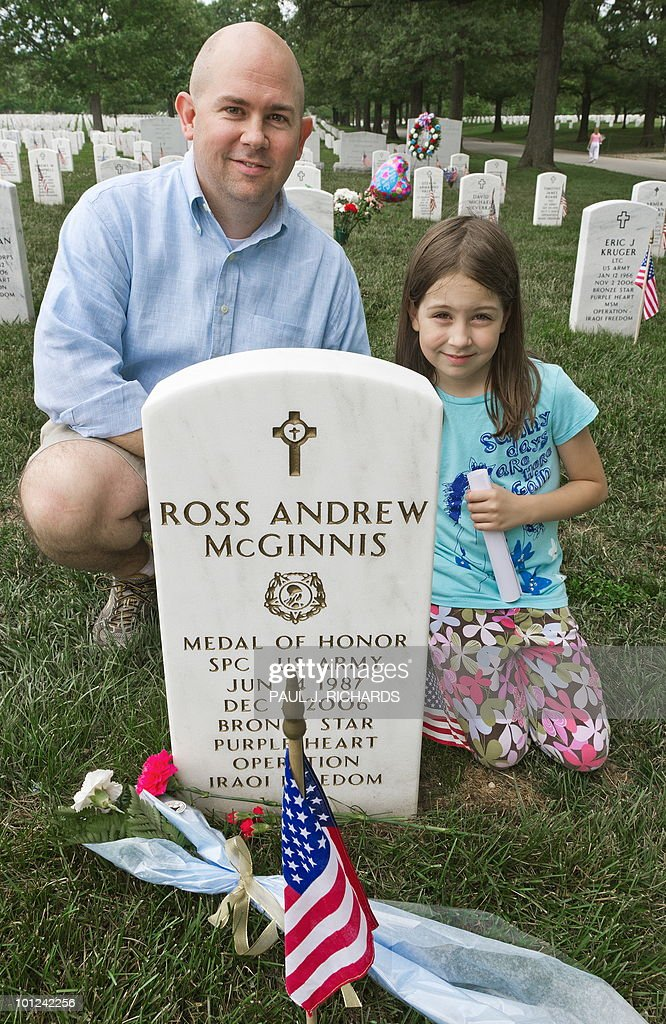 Arlington, Virginia, resident David Presson, who asked for a keepsake photo, takes his daughter Abigail, 8, on a 'history & life' lesson and visit Arlington National Cemetery May 28, 2010, placing flowers at the gravesite of US Army Pfc. Ross A. McGinnis, whom they have no direct connection with, and who earned the Silver Star Medal for taking the force of a grenade explosion to save his fellow soldiers in Baghdad on December 4, 2006. Presson and his daughter researched heroic US soldiers and is reading the entire record of McGinnis's heroism, from his Iphone. They visited several heroic fallen soldiers gravesites as part of his Memorial Day 'history & life' lessons with his daughter. AFP Photo/Paul J. Richards