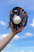 Female arm holding baseball with glove in blue sky. This photo has the concept of winning or success. With catching the ball in sport, you usually score some points. On the background of the image you