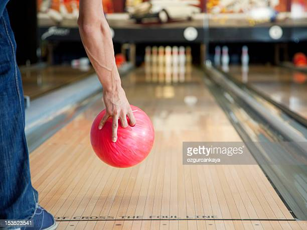 Arm holding red bowling ball above skittles alley