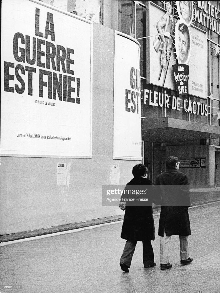 Arm in arm, a couple walk past posters that read 'La Guerre est Finie! Si Vous le Voulez. John et Yoko Lennon vous souhaitent un Joyeux Noel,' on the Champs Elysees, Paris, France, December 21, 1969. The poster translates as 'War is Over! If You Want It. John and Yoko Lennon Wish You a Merry Christmas.' The theater at right advertises the Walter Matthau film 'Cactus Flower' ('Fleur de Cactus') on it's marquee.
