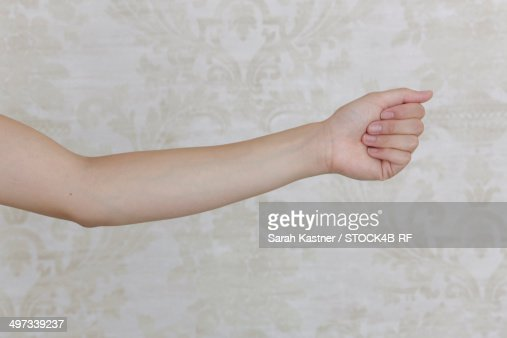 Arm of a woman in front of patterned wallpaper