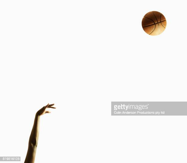 Arm of Black basketball player shooting ball