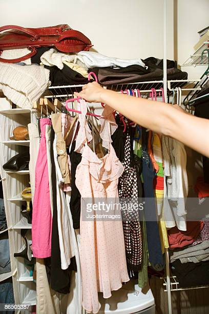 Arm  of woman holding dress in closet