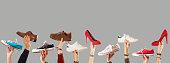 arm raised holding shoes