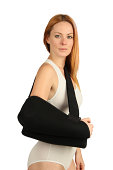 Young woman has an arm sling after shoulder surgery