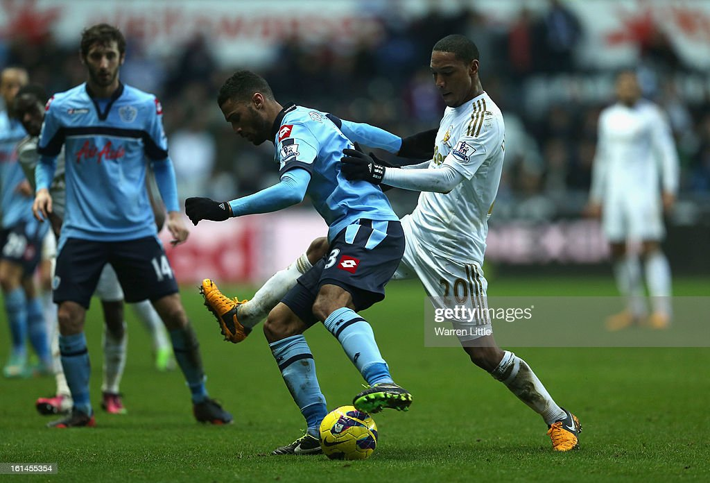 Armand Traore of Queens Park Rangers is tackled by Jonathan de Guzman of Swansea City during the Premier League match between Swansea City and Queens Park Rangers at Liberty Stadium on February 9, 2013 in Swansea, Wales.