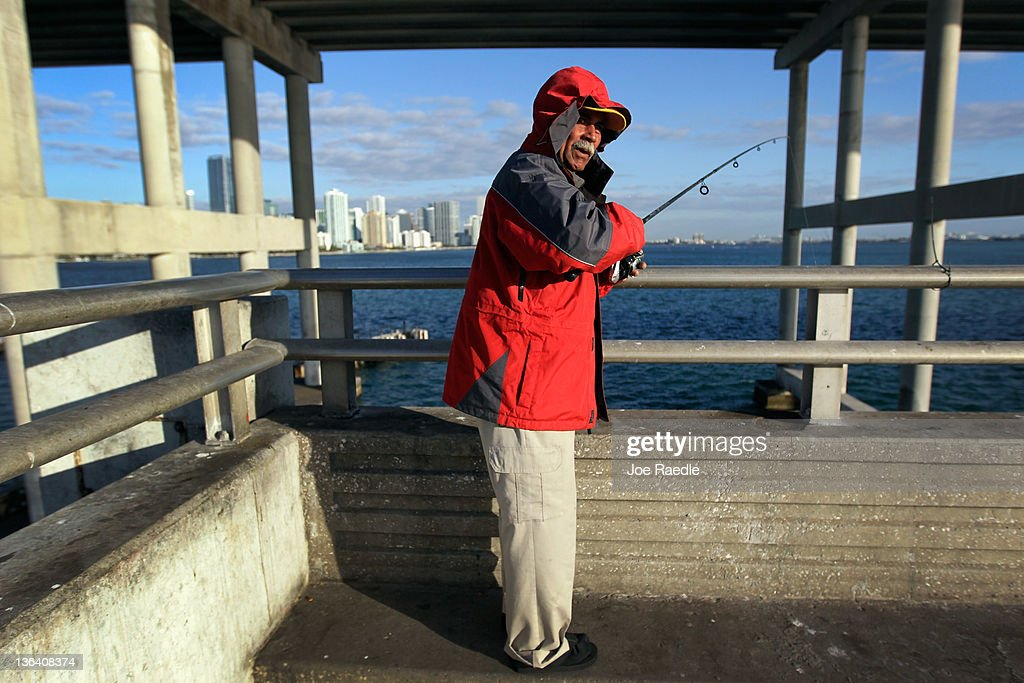 Armando Contrera bundles up against the cool weather as he fishes on January 4, 2012 in Miami, Florida. South Florida experienced one of the coolest days of the winter season last night but temperatures are expected to warm up.
