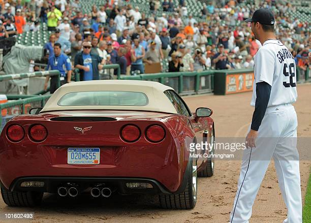 Armando Galarraga of the Detroit Tigers looks over his new Chevrolet Corvette awarded to him by Chevrolet for his near perfect game the night before...