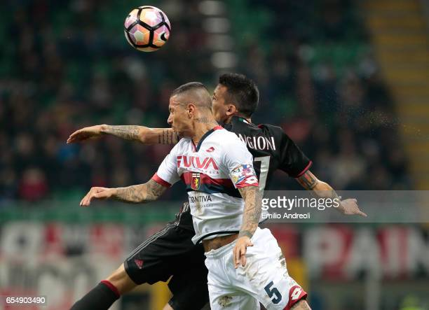Armando Izzo of Genoa CFC jumps for the ball with Leonel Vangioni of AC Milan during the Serie A match between AC Milan and Genoa CFC at Stadio...