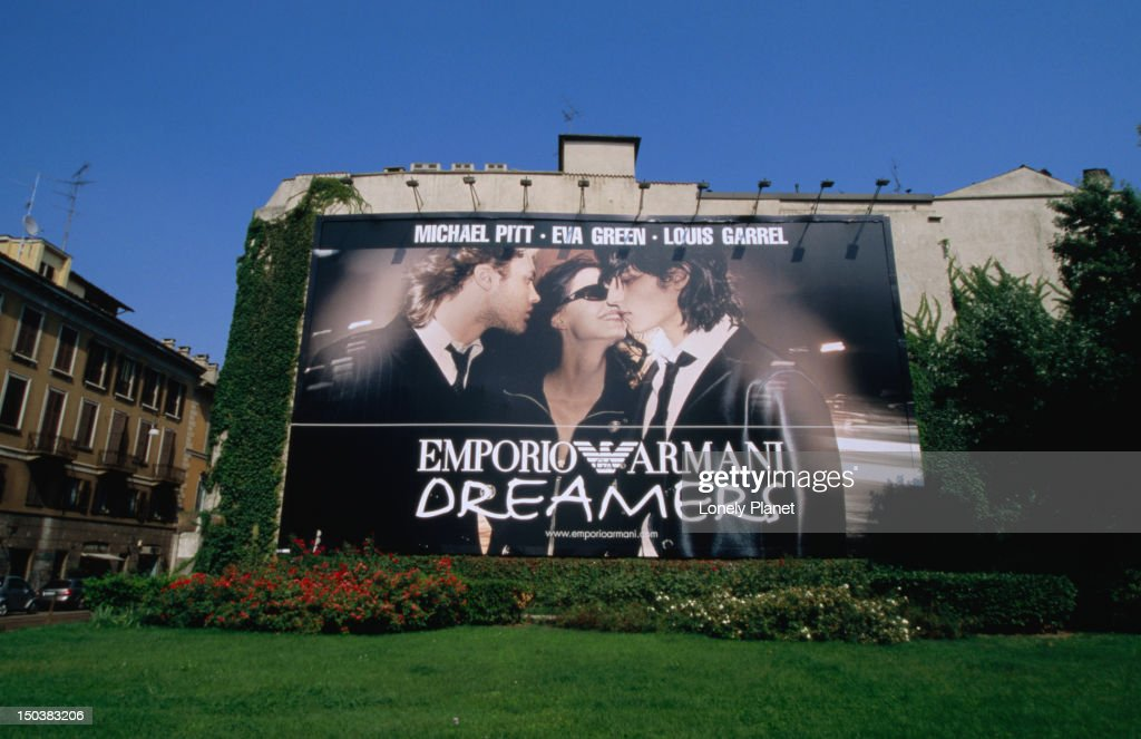 Armani advertisement on house wall in front of Armani-sponsored lawn, Via Mercato. : Stock Photo
