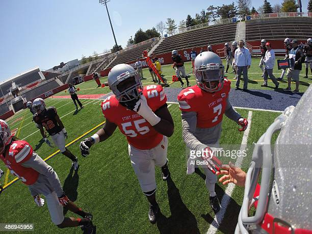 Armani Garrick and Tyrice Beverette of Stony Brook celebrate a play with Quarterback Conor Bednarski their Spring Football Game at Kenneth P LaValle...
