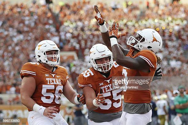 Armanti Foreman of the Texas Longhorns celebrates with teammates after scoring a touchdown during the first quarter against the Notre Dame Fighting...