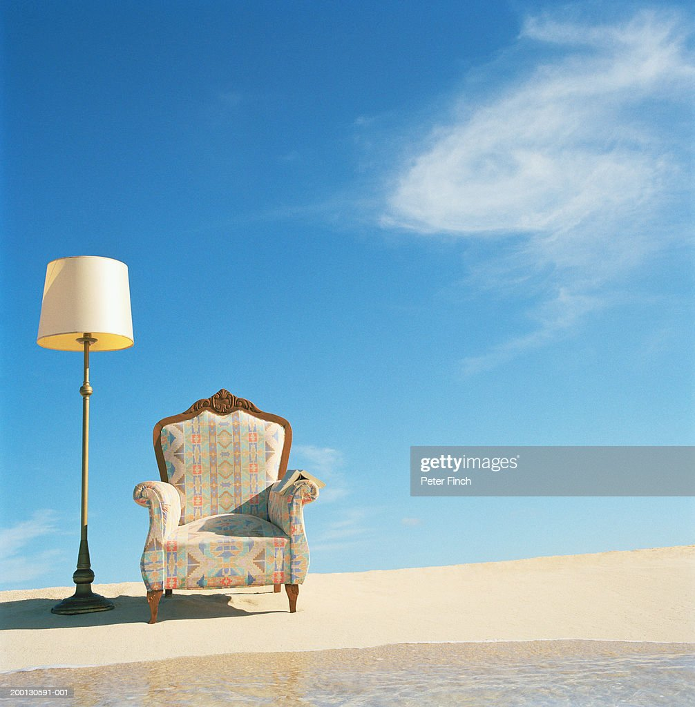 Armchair and lamp on beach by surf : Stock Photo