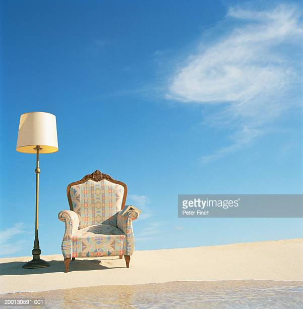 Armchair and lamp on beach by surf