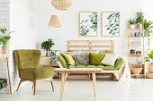 Green armchair next to wooden table in floral living room with lamps and pillows on sofa against white wall with leaves posters