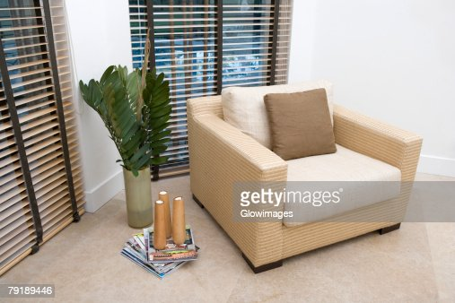 Armchair with decorative paper weights on magazines in a living room : Foto de stock