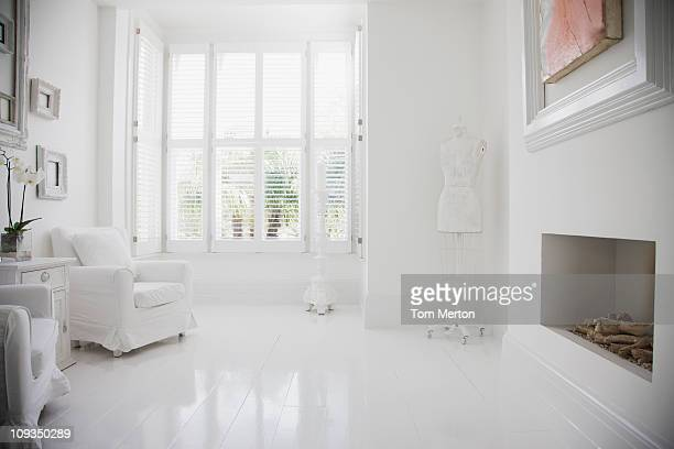 Sessel und Kamin in einer eleganten, weißen Wohnzimmer