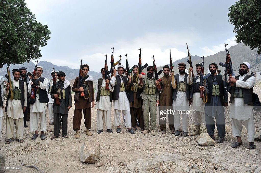 Armed Afghan villagers raise their weapons as they vow to defend their village against the Taliban in Sor Kandaw village Dur Baba district of...